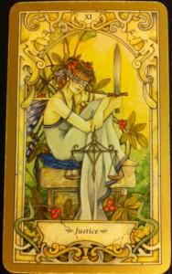 Tarotová karta Justice (Spravedlnost). Má zavázané oči, aby byla nestranná a v rukou drží váhy...